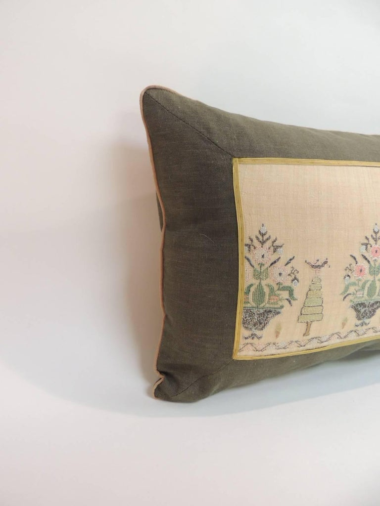 19th century Turkish embroidery lumbar pillow. Turkish linen and silk embroidery lumbar pillow. Depicting flowers and trees, decorative gold trim across the linen frame. Green linen frame and backing. Small tan color rope trim all around. Pillow