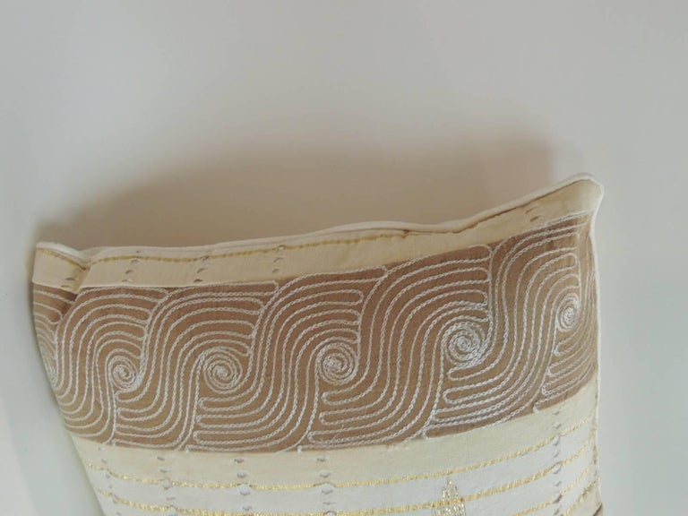 Pair of vintage striped embroidered African bolster decorative pillows.pillows in shades of natural and camel color striped and embroidered with metallic gold threads over eyelet textile panels.  The embroidery is linen on silk.  Natural color trim