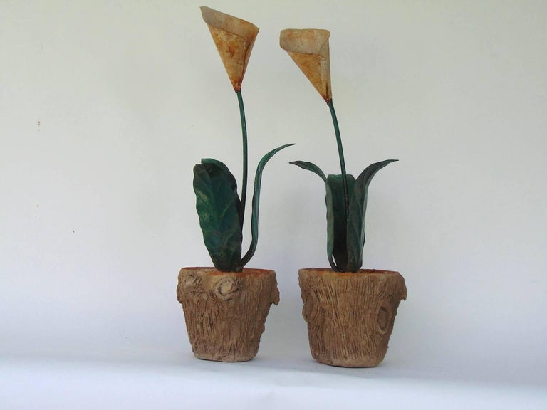 Stunning very similar pair of decorative tole peinte calla lilies in concrete faux bois jardinières, one slightly taller than the other. Very realistic treatment of wood on the pots. The smaller of the two is 29.5