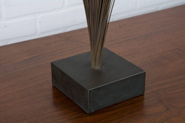 This vintage midcentury sculpture is in the style of Harry Bertoia's spray sculpture. It features a slate base and metal rods with a bronze finish that 'spray' out from the base.