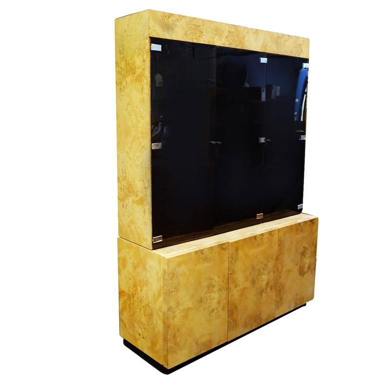 Large Postmodern burl elmwood cabinet featuring a breakfront with three smoked glass doors containing adjustable shelves inside and three cabinets underneath. There are three recessed lights along the inside of each cabinet.  This cabinet was made