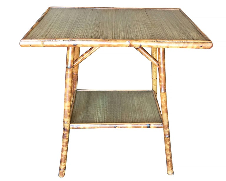 Antique tiger bamboo pedestal side table with rice mat top and secondary bottom shelf.  Restored to new for you.  All rattan, bamboo and wicker furniture has been painstakingly refurbished to the highest standards with the best materials. All