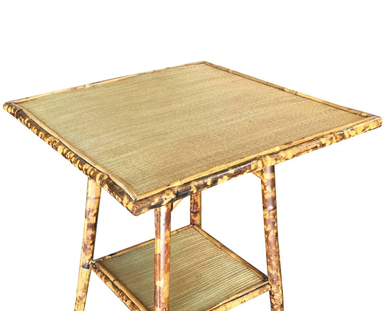 Antique tiger bamboo pedestal side table with rice mat top, large top and secondary bottom shelf.   Restored to new for you.  All rattan, bamboo and wicker furniture has been painstakingly refurbished to the highest standards with the best