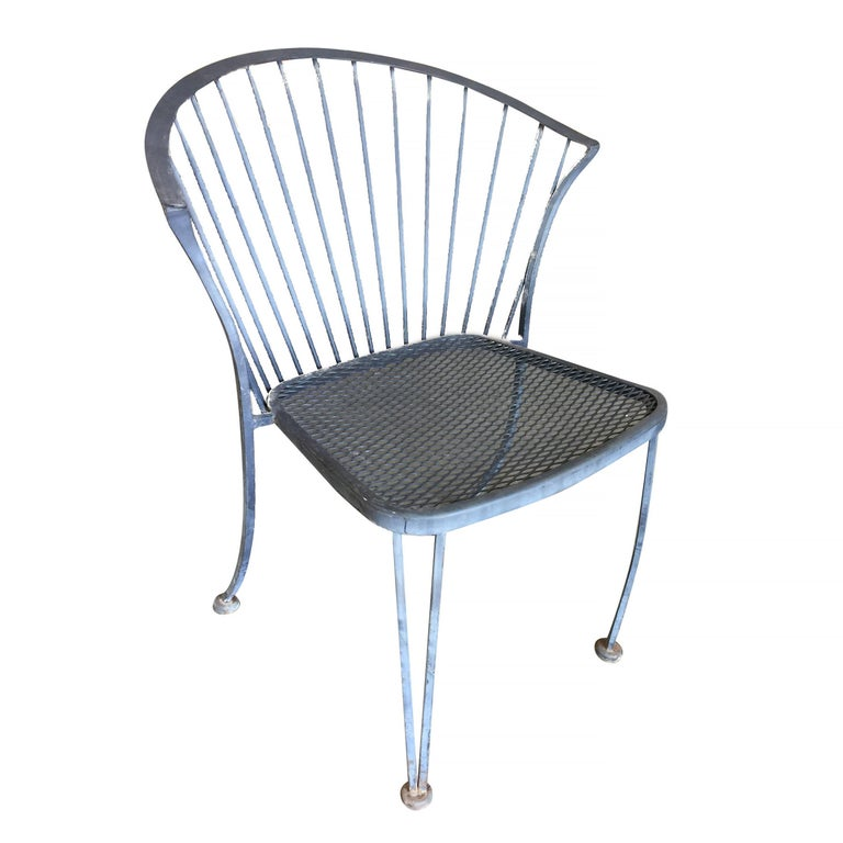 Set of four Woodard Pinecrest rod iron outdoor/patio chair with distinct curved modernist backrest. This chair is constructed with solid core iron rods finished in a pure white finish and a padded seat.  Available.