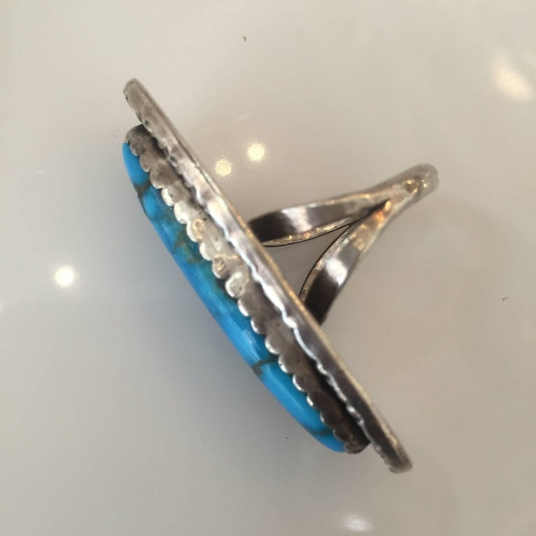 Vintage Southwest style bell trading post ring with a sterling silver band and a large turquoise stone.