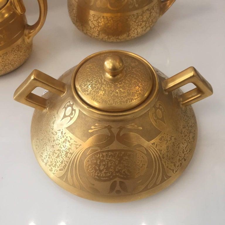 Set of five 18-karat plated porcelain table tea set with bowl, creamer, sugar, large sugar dish signed Osborne with Candlestick signed Limouge.  Measure: Candlestick H 7 in. x W 3.5 in. x D 3.5 in. Bowl H 2.5 in. x W 8.5 in. x D 8.5 in. Sugar H