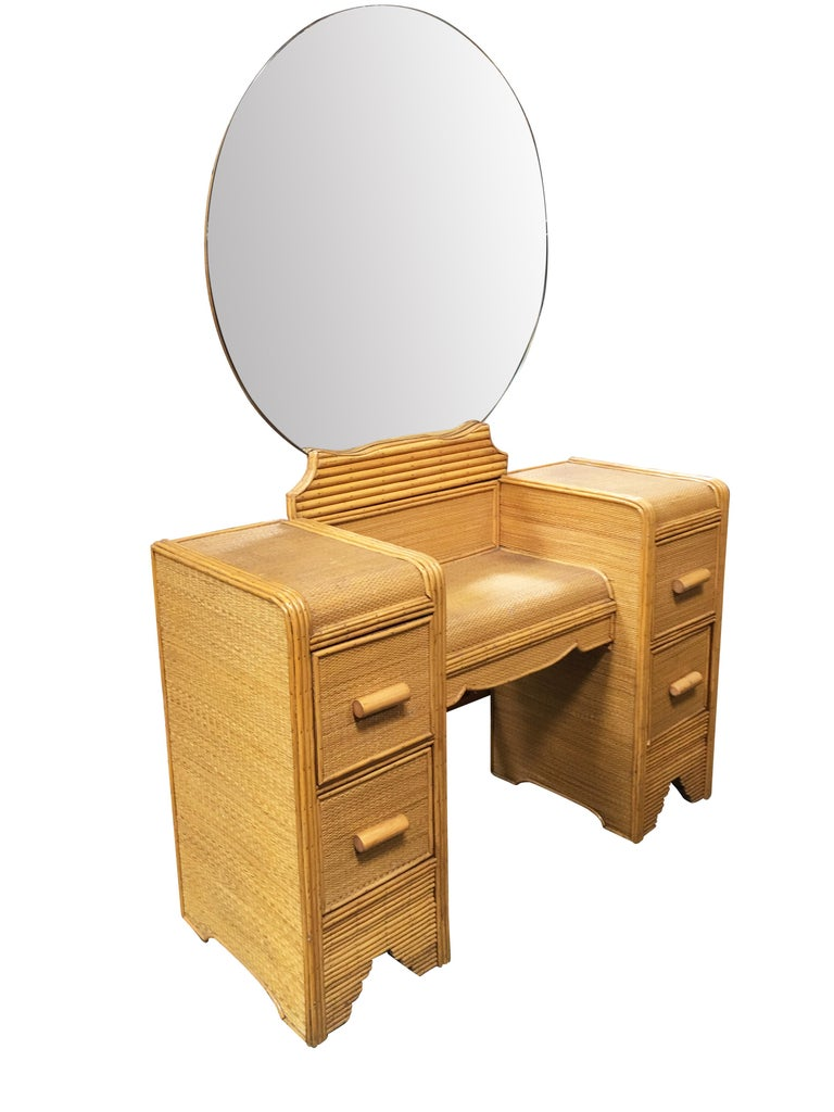 Stick rattan vanity with woven rice mat coverings and round rattan mirror. The vanity features decorative nail heads, larger vanity mirror and four side pull out drawers. 