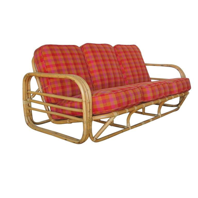 Streamline Art Deco rattan living room set which includes one lounge chair and a matching three-seat sofa.  Each seat features rounded three strand rattan arms with three decorative horizontal bars running through the center of each arm along with a