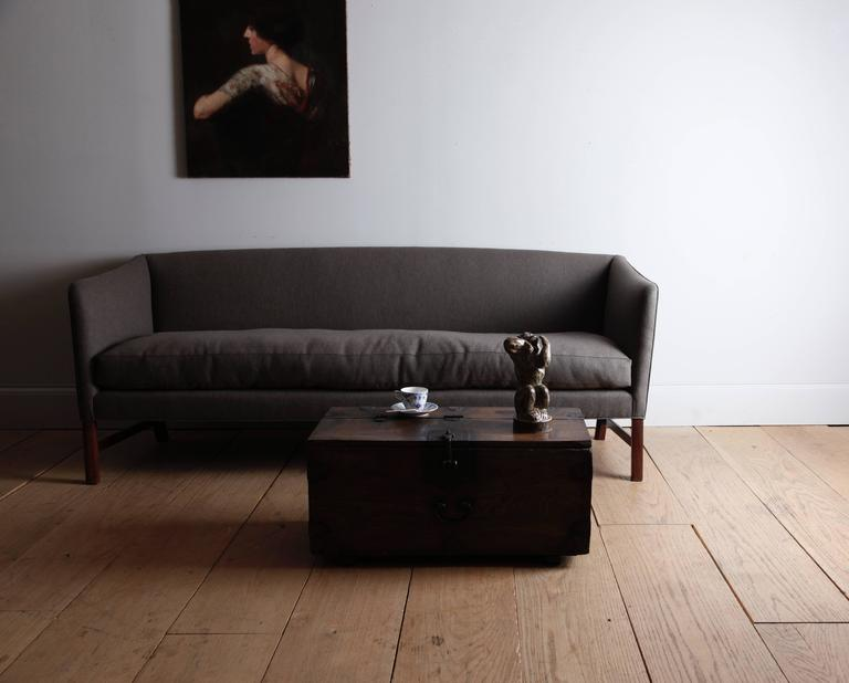 A beautifully balanced design. The influence of English--especially Regency--furniture on Wanscher and his teacher Kaare Klint is quite evident in the form of this sofa. The high arms slope gracefully down from a wide, smooth back. We have