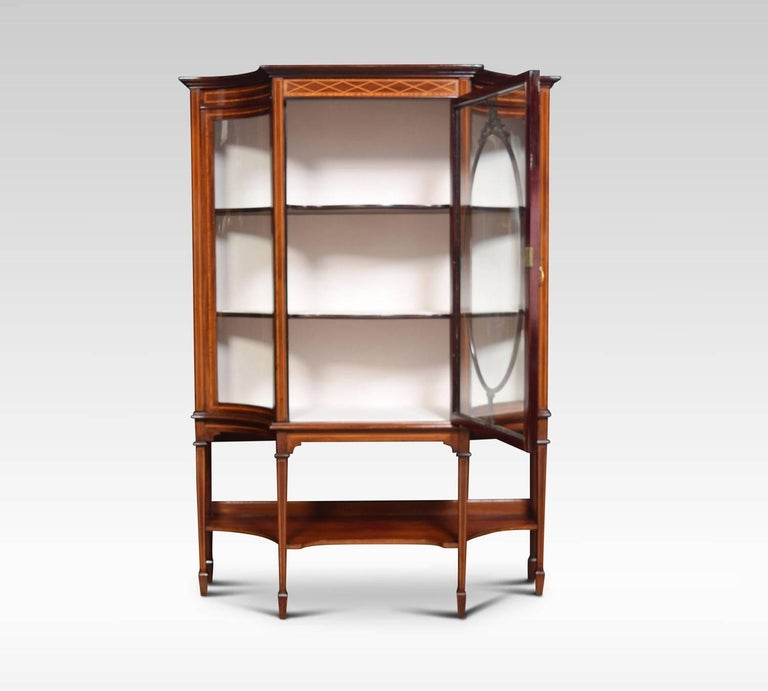 Edwardian inlaid mahogany display cabinet, the central glazed panel door decorated with carved leaf and ribbon motifs enclosing upholstered interior fitted with two fixed shelves, flanked by inverted bowed glazed panels, raised on square tapering