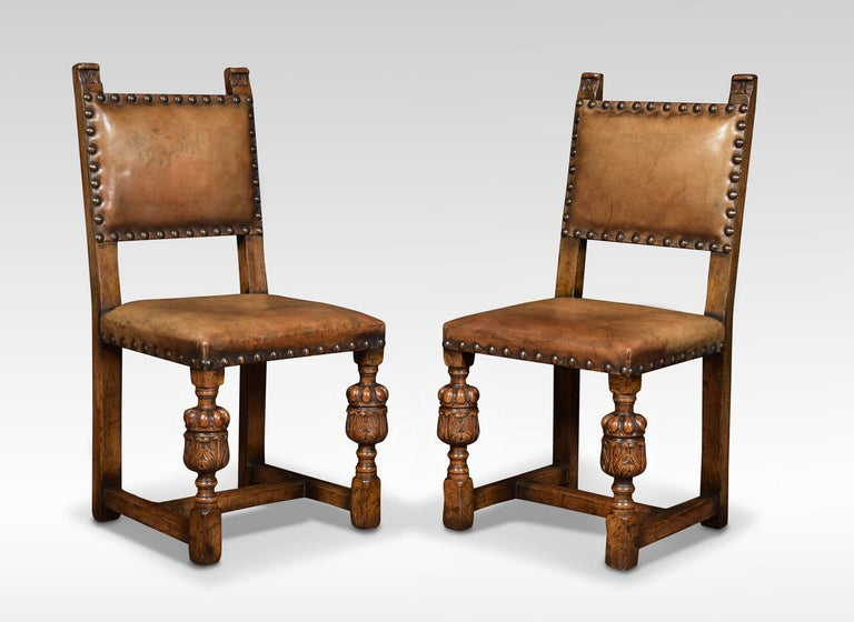 Set of eight oak dining chairs, the square upholstered studded backs above overstuffed seats all raised up on gadrooned bulbous cup and cover legs united by stretcher.