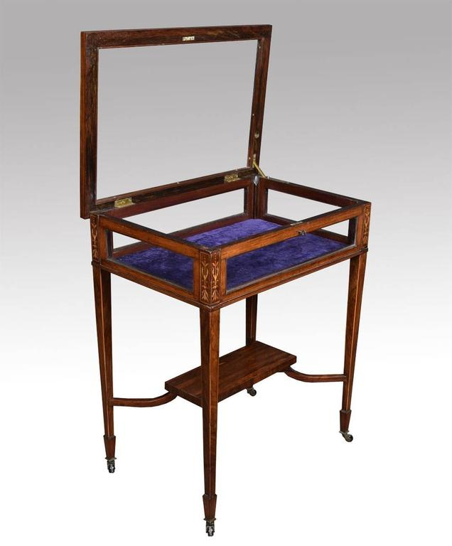 Edwardian rosewood and inlaid rectangular bijouterie display table, bordered with boxwood lines and decorated with foliate scroll designs, having a hinged glazed panel top and glazed panel sides all raised up on square tapered legs terminating in