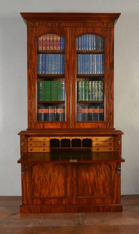 Victorian mahogany secretaire - bookcase, the ogee cornice above a pair of arched glazed doors, enclosing four adjustable shelves, the projecting base with secretaire drawer opening to reveal fitted interior and leather inset above a pair of arched