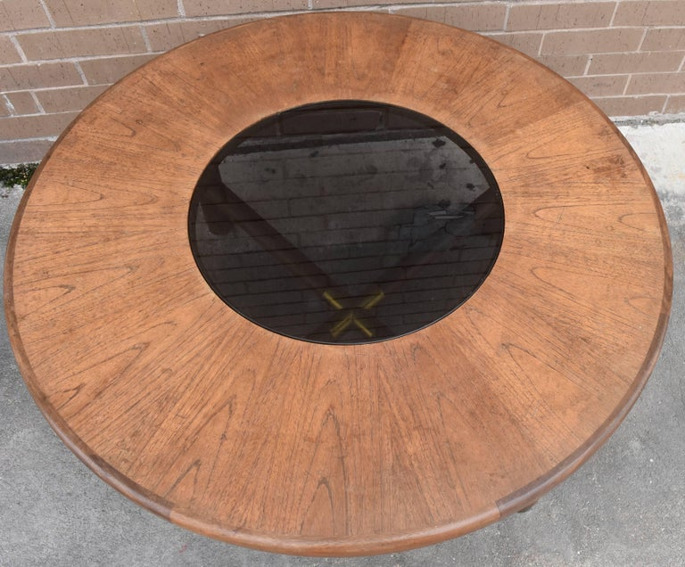This is a beautiful round wood and glass coffee or cocktail table with brass fittings on the legs and center stretcher. The diameter of the glass inset 18