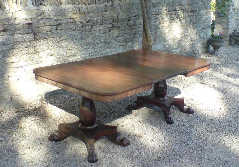 Early 19th century mahogany twin pillar antique dining table standing on four splay platform base, made of very good cut of timber with excellent grain pattern and with original leaf. Can take another leaf if required,   English, circa