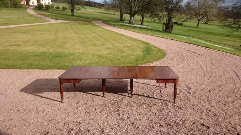 19th century George IV period antique dining table. This table is made of mahogany that has faded to a very desirable golden brown color with good patina. The legs are at the corners of each and tucked away in the centre so that no one has a leg in