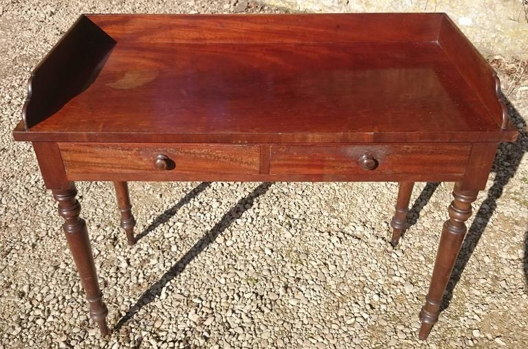 19th century mahogany serving table, side table or dressing table with gallery to stop things falling off the back. This is very useful for all applications, but especially when used as a dressing table as it stops the mirror being pushed too far