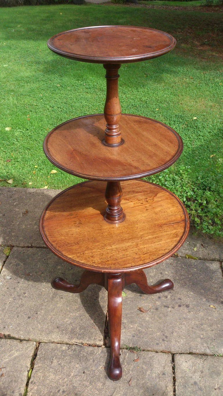Charming George III mahogany three-tier antique dumb waiter or antique whatnot. Very useful at chair side for holding drinks, remote control, books or in the corner of a room to display plants or photograph frames. This is an elegant early version