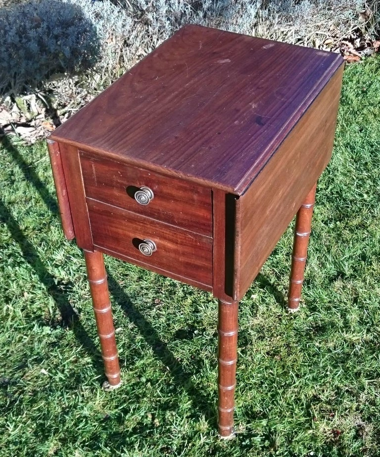Early, 19th century Regency mahogany antique bedside cupboard. This cupboard has good Regency proportions with slender legs and good dovetails. The casters and handles appear to be original. The legs are simulated bamboo which was a popular device