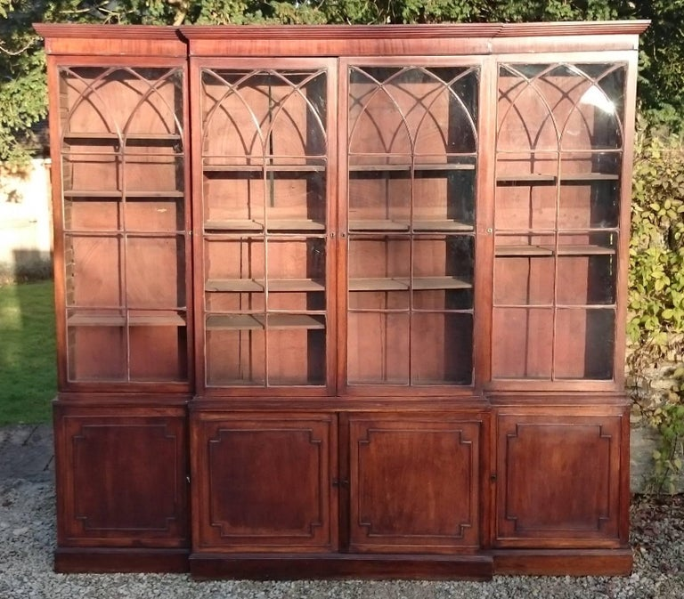 Large antique bookcase made of good South American mahogany. It has eight doors, four glass for display and four blind to hide things, behind which are adjustable shelves. The doors and astral glazing bars are typical of this early period of cabinet