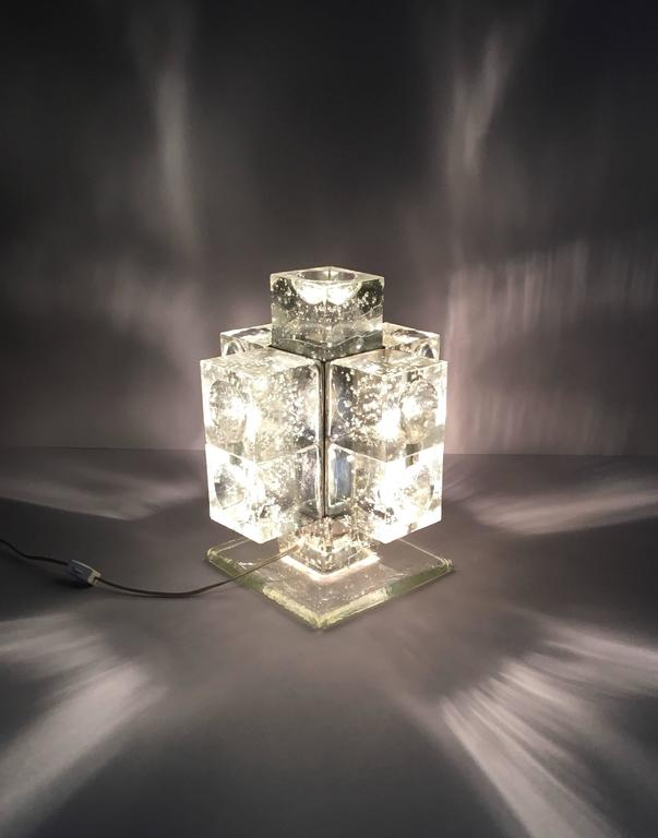 This is an early production Poliarte light. The cube shaped glass has only one side with the cut hemispheric groove. The cube was later changed to have a groove on all sides. The light is made with a cast glass base, one internal light socket and