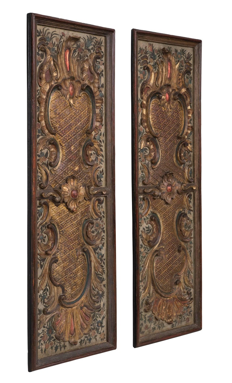 A handsome pair of Italian early 19th century Baroque st. painted, polychrome and gilt carved decorative panels. The true pair have an elegant painted foliate background. The center of each panel has a boldly carved rosette amidst scrolls. Both are