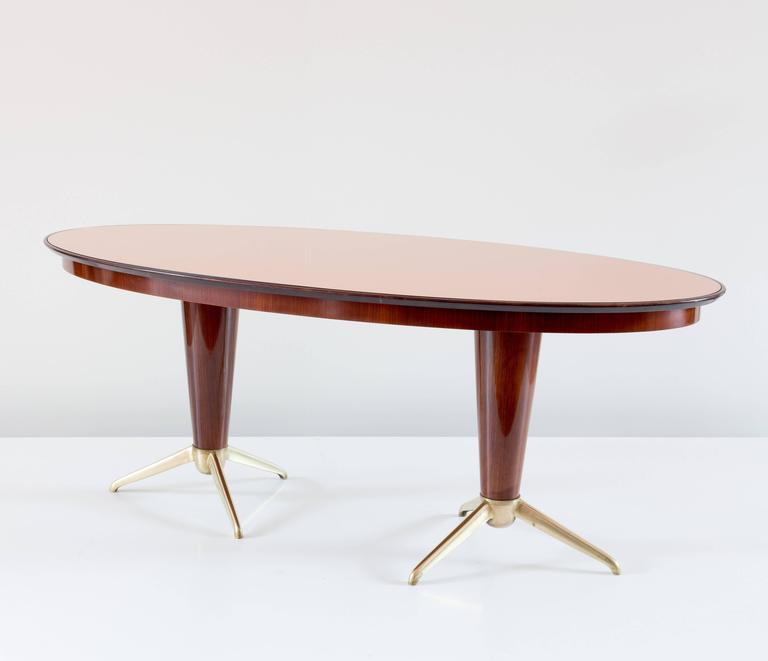 Rare mahogany dining table attributed to Melchiorre Bega, circa 1952 oval top in mirror rose glass, two central feet with six brass legs mahogany veneer. Perfect original condition. Measures: H 78 cm, 195 x 99 cm.  Literature: Aloi, Esempi di