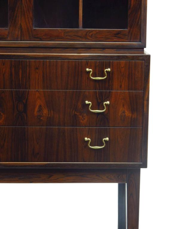 Danish rosewood china cabinet in manner of Ole Wanscher. Features a three-drawer cabinet with brass pulls and locking glass hutch. Dark figured rosewood with pattern match down front of drawers. Glass doors opening to a rosewood lined interior with