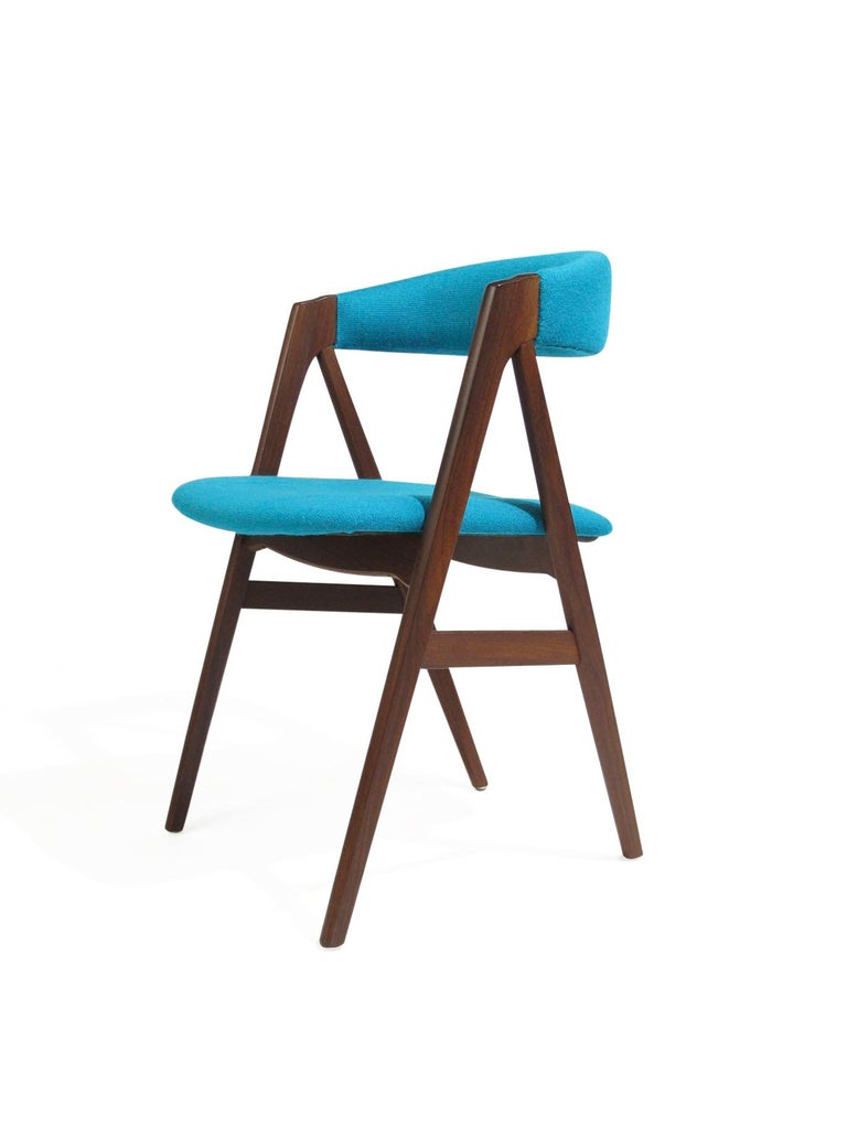 Four midcentury dark teak dining chairs with comfortable curved backrest on a sturdy teak A-frame. Newly upholstered in a high-quality turquoise aqua blue wool textile over new foam. The wood has been professionally restored and in excellent