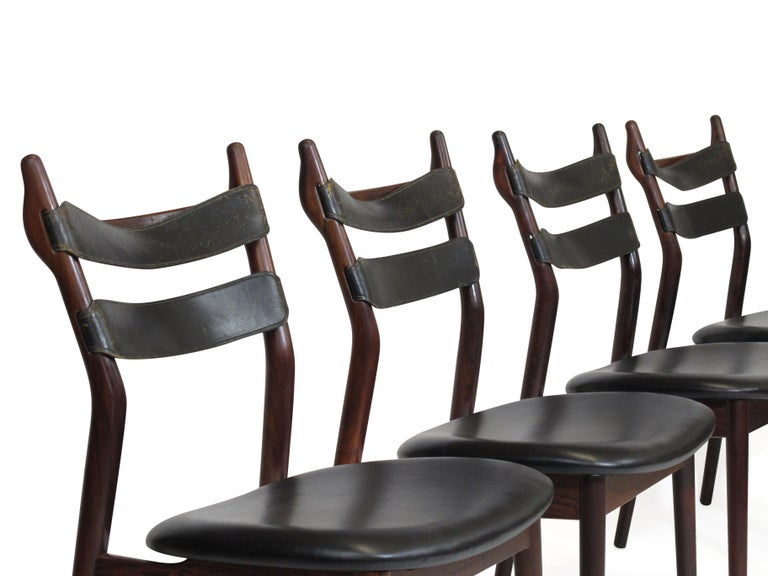 Set of four midcentury rosewood dining chairs designed by Helge Sibast. Solid rosewood frame with original black leather strapped bask rest and newly upholstered seats in black leather.