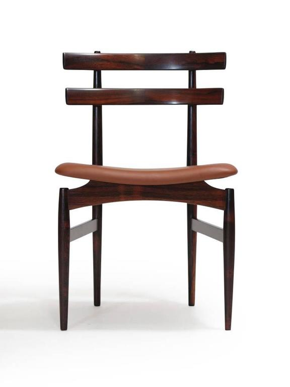 Ten finely crafted Mid-Century rosewood dining chairs, model #30, by Poul Hundevad & Co. Features sculpted, solid rosewood with rich grain, and exquisite joinery. The floating seats are raised on an elegant frame structure with tapered legs.