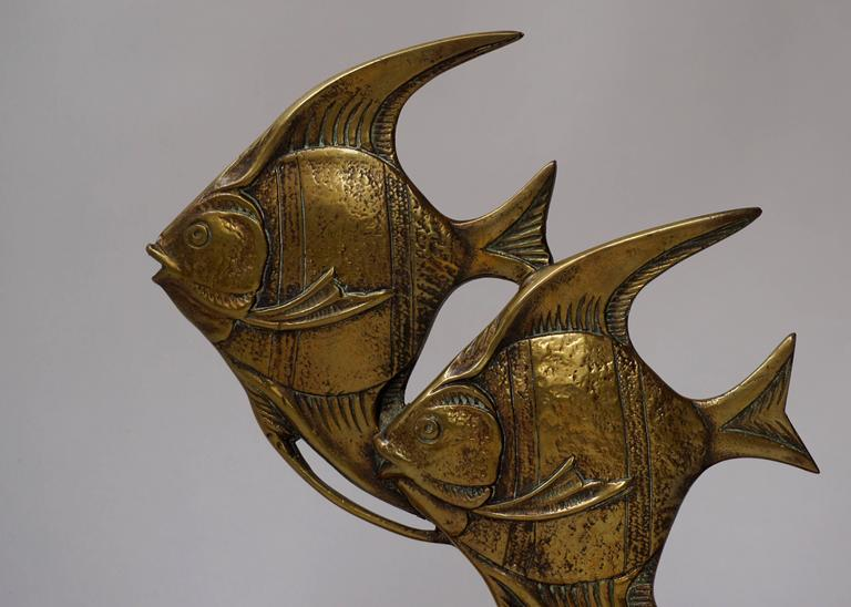 Brass fish sculpture on marble base.