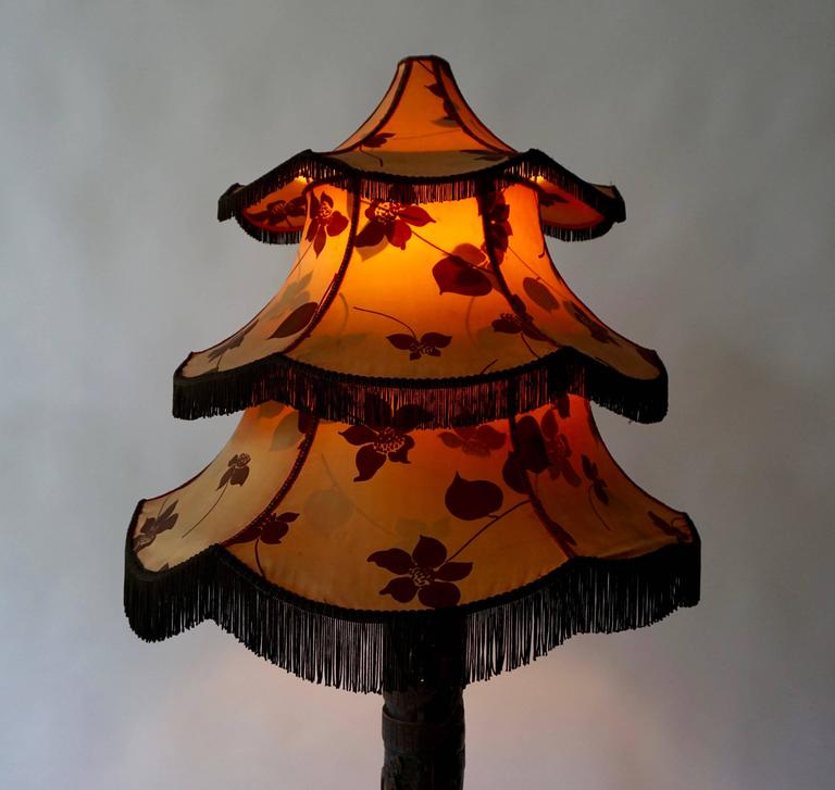 Chinese floor lamp. For your consideration an antique table lamp. Hand carved flower sculpture base in solid rosewood with a beautiful original pagoda shade decorated with flowers. China circa the 1920s.Wood in good shape. Nice details on the