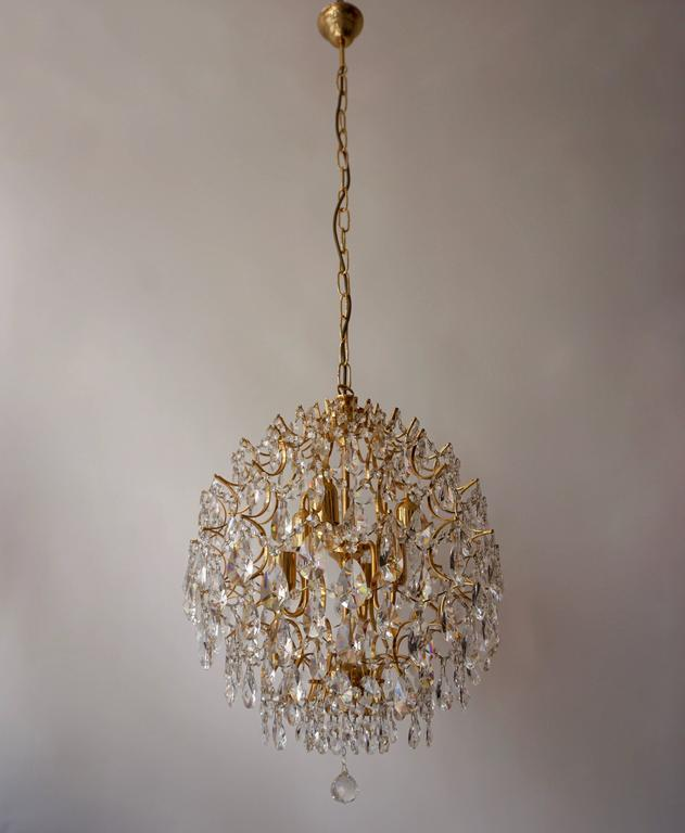 Italian chandelier in brass and crystal glass. Measures: Diameter 50 cm, height 60 cm, height with the chain is 120 cm. Six E14 bulbs.