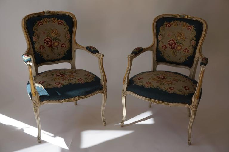 A very pretty set of two armchairs with a soft grey and gold painted surface of Louis XV design but circa 1950s, the tapestry work of exceptionally delicate form and in fairly good condition on well-shaped scroll supports.