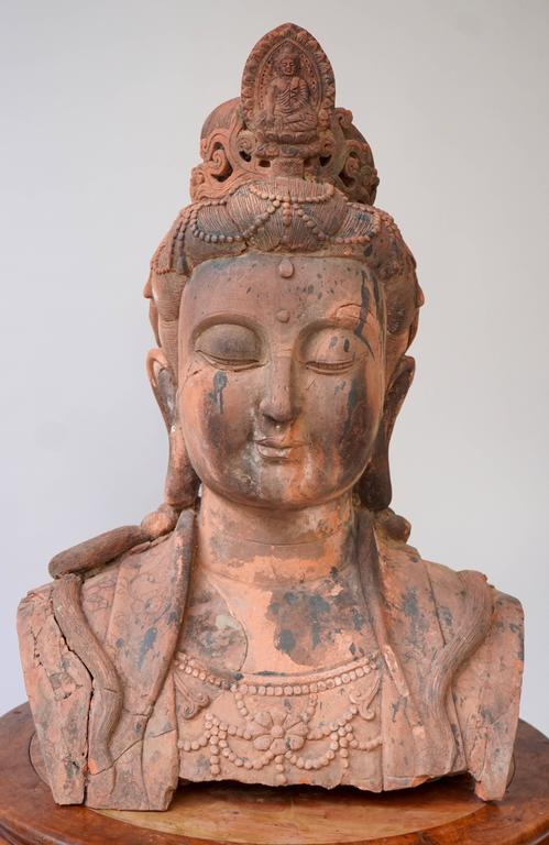 A massive larger than life terracotta bust of Guan Yin, China, early 20th century. Broken and restored with wear and tear from enduring exposure to the elements. Size: 75 cm high. Weight: 40 kg.