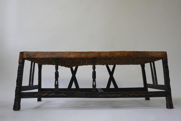 A fine and elegant hardwood Chokwe (Angola) bench, carved all-over with geometric patterns, human and animal motifs. The front rain supported with caryatids in the form of male figures of which one is missing. Original parchment cover, late 19th