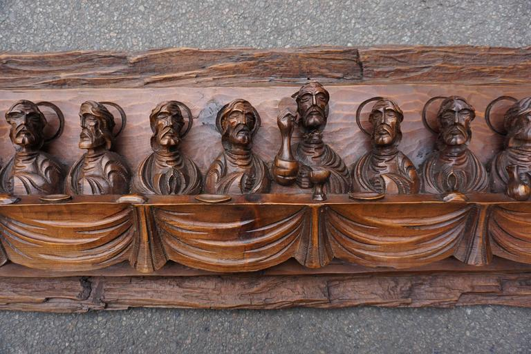 A wood carving representing the Last Supper with Judas, with Jesus amidst 11 disciples seated on either side at a long table. The head of Christ has been broken off and replaced, circa 1950. Dimensions: Width 115 cm. Height 30 cm. Depth 8 cm.