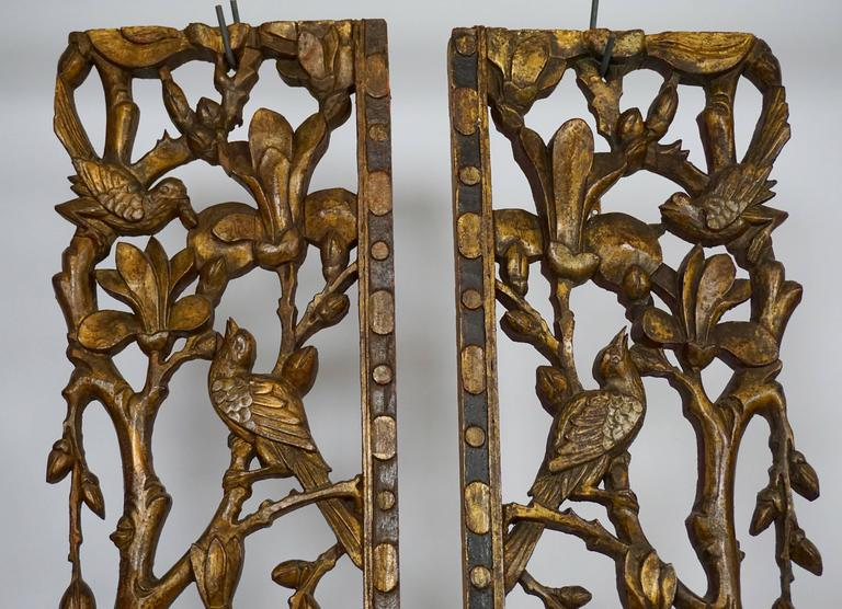 A pair of carved giltwood mandarin bed ornaments in the form of ' à jour ' – carved courting birds amidst flowering magnolia branches in spring time.