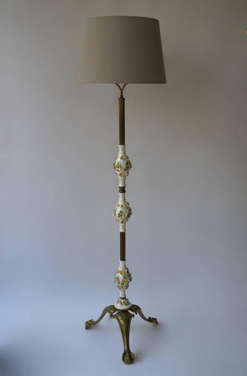 Beautiful Italian brass and porcelain floor lamp. The lamp has a lovely porcelain with beautiful flowers. The shades are not included in the price.. Brass has some patina. Height with shade 175 cm. Diameter Shade 44 cm. Diameter base 45