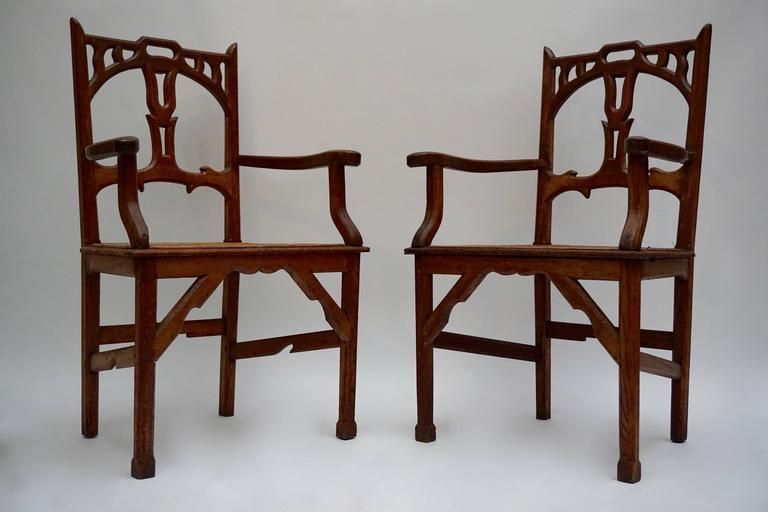 Pair of Art Nouveau carved teak armchairs with wicker woven seats.