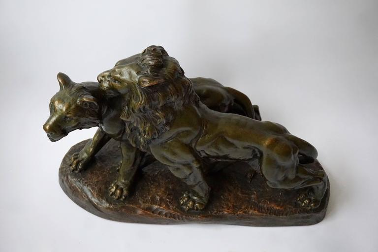 Art Deco terracotta lions mounted on rocky rectangular plinth. Signed. Measures: Height 45 cm, width 67 cm, depth 30 cm.