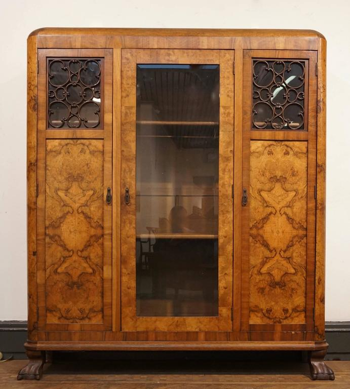 This beautiful walnut armoire features a central door front flanked by two doors, which open to shelved storage. (Two shelves).