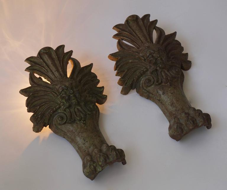 Two cast iron wall lamps in the shape of a man's heads and lion claws.  Measures:  Height 36 cm. One E14 bulb.