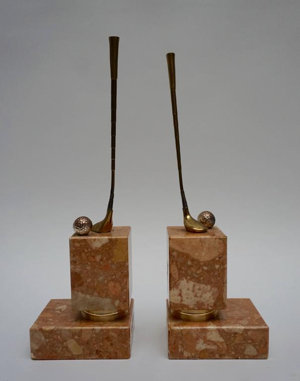 A pair of red Italian Breccia marble, gilt, silvered and brown patinated bronze bookends, representing the sport of golf.