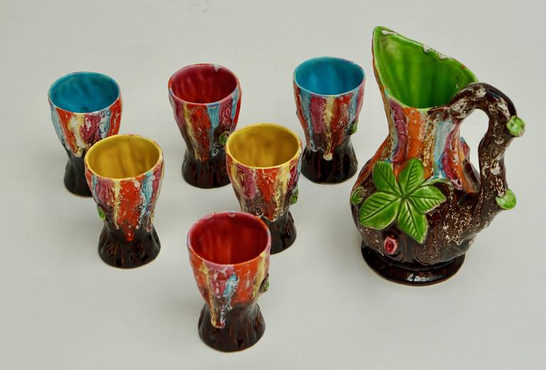 Drinking set composed of a jug and six glasses in ceramic.  The jug is signed.  Jug dimension: Height 26 cm, depth 16cm, width 20 cm. Glass dimension: Height 13cm, diameter 8cm.