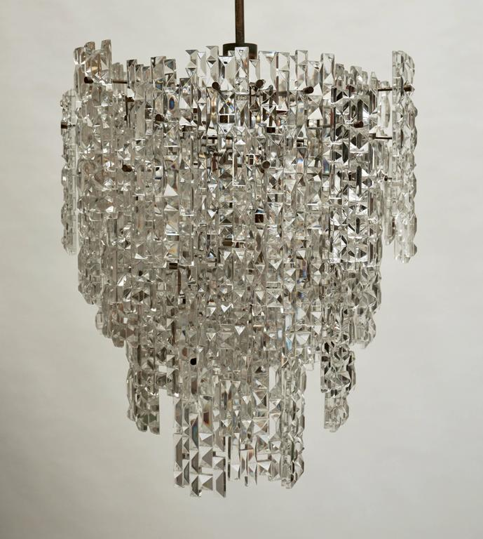 A magnificent modern crystal chandelier by Kinkeldey with 65 asymmetrically faceted crystals. Stunning size and quality ! Nine E14 and one E27 bulbs. Measures: Diameter 48 cm. Height fixture 55 cm. Total height 110 cm.