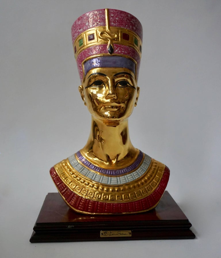 Polychrome porcelain bust of Nefertit by Vittorio Sabatini, after the 1340 BC original in the collection of the Egyptian Museum of Berlin, depicting the Sun Queen wearing a flat-topped crown decorated with a uraeus, the ancient symbol of divine