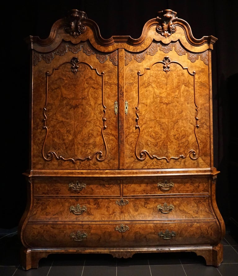 A very fine and rare burr walnut and walnut double domed cupboard; Holland, circa 1700. Resting on bracket feet, the base has two large drawers a pair of half - width drawers, protruding on the bottom and inlaid with crossbanded geometric ornament.