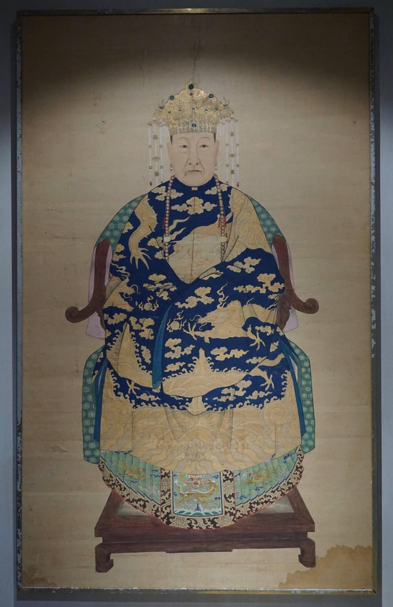 A fine Chinese painting on silk, representing a lady of class in her dragon robe and gold and pearls crown, seated on a huanghuali armchair, her feet resting on a huanghuali and marble footstool,18th-19th century. As silk is a very fragile fabric